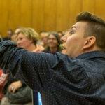Mann vor Publikum zeigt mit Arm an die Seite
