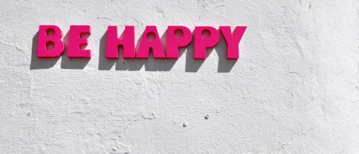 """Schriftzug """"be happy"""" auf einer weissen Wand"""